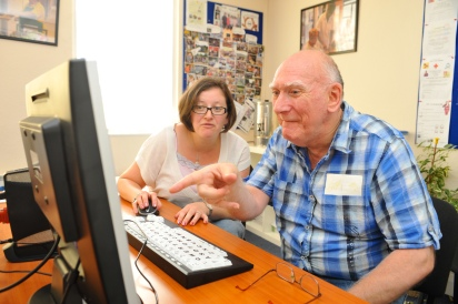 A tutor helps an adult learner increase his digital literacy.